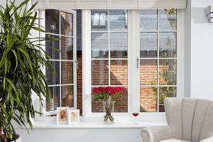 White casement windows with flowers and wine glass on ledge