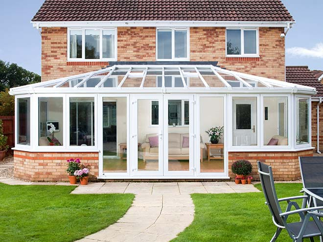 Large white conservatory on brick two storey home