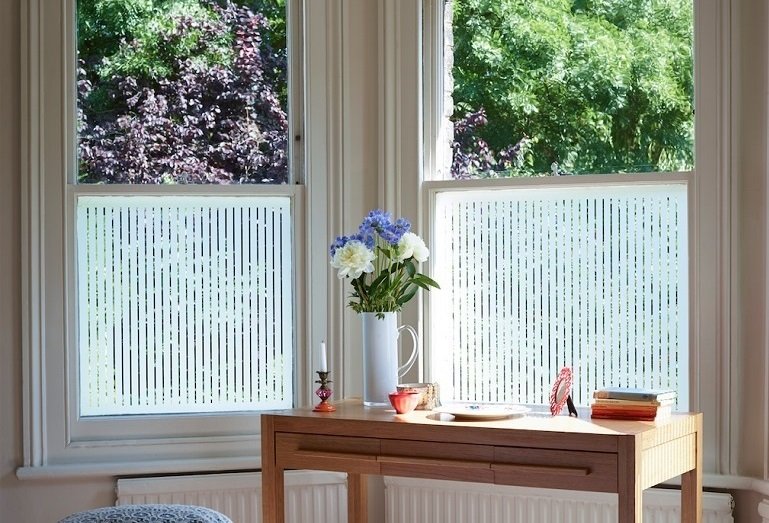 Window film on bedroom windows, table and vase with flowers