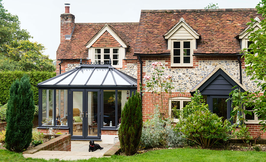 grey wooden conservatory beside brick home