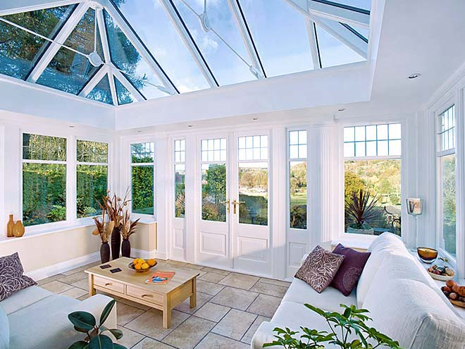 Inside timber conservatory with furniture, garden view