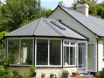 victorian conservatory with grey tiled roof by just windows and doors