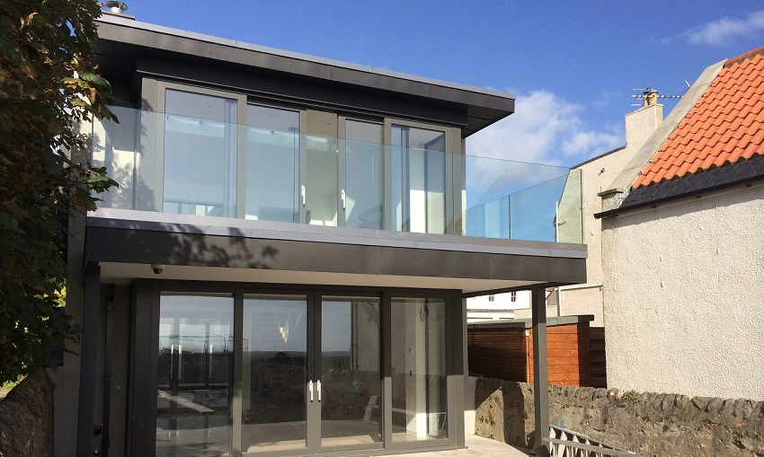 two storey home with glass doors and balustrade