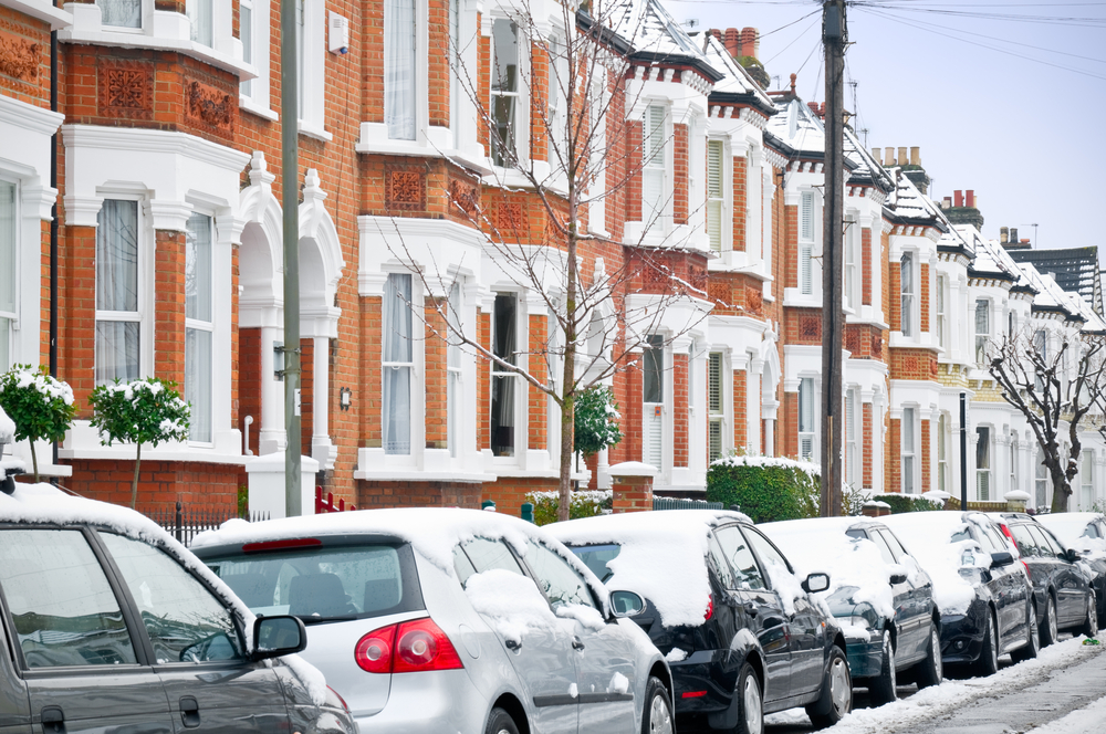 cars parked on house lined street in winter with snow