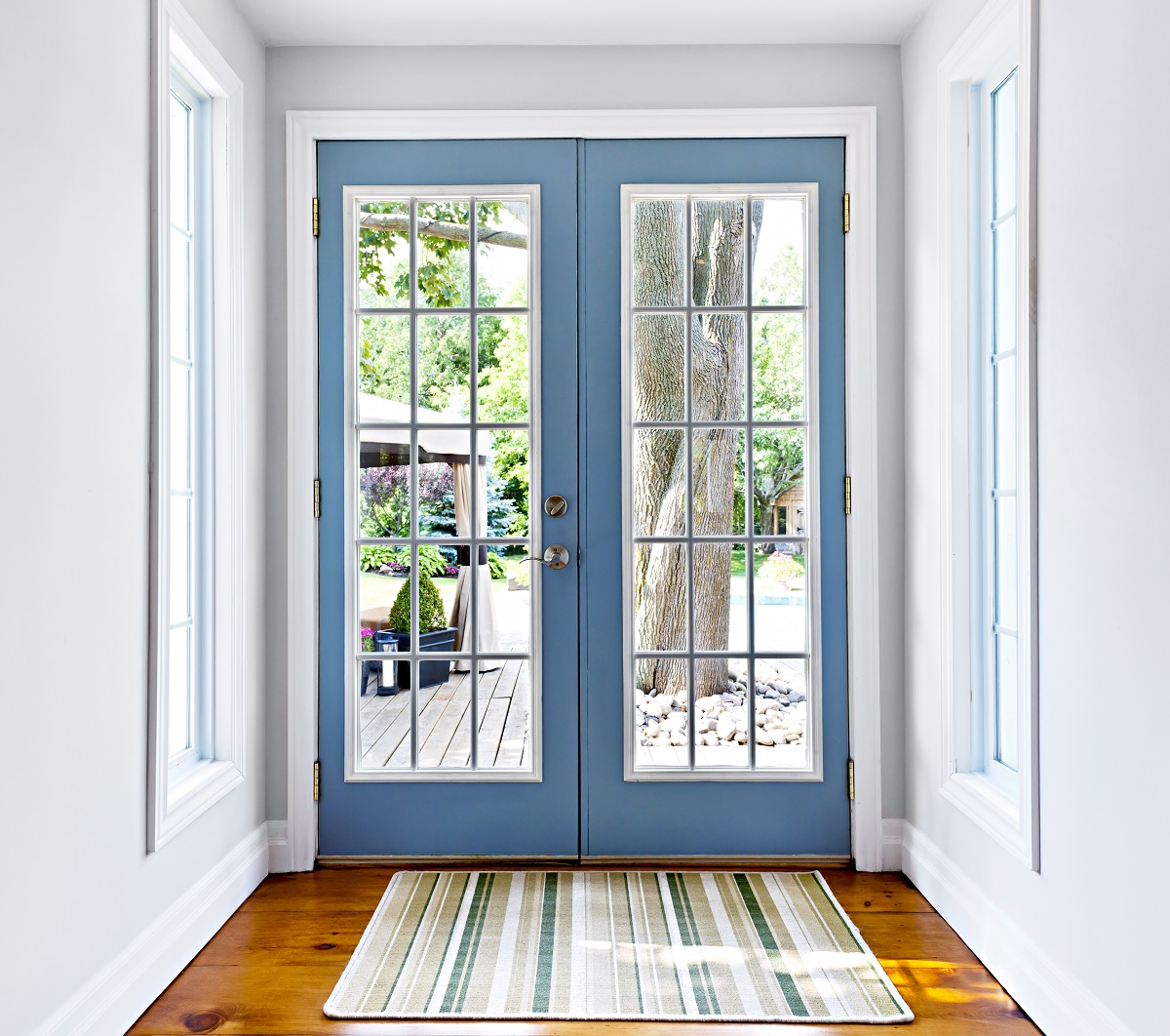 blue framed glass doors with doormat and tree