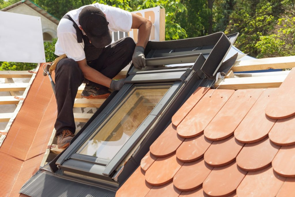 man on tiled roof installing window