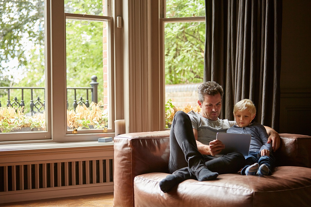 Shot of a father and his young son sitting together on the living room sofa using a digital tablet