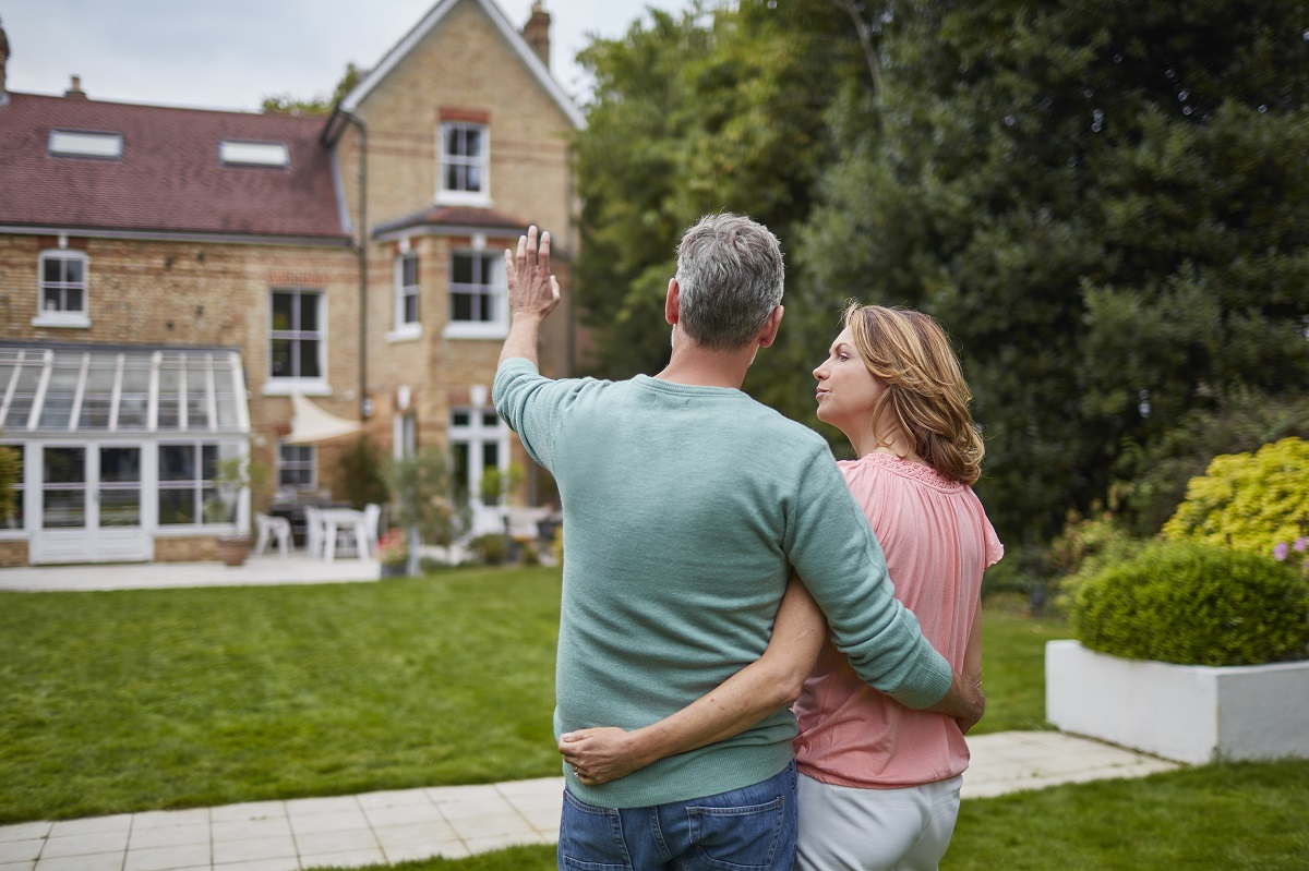 Rear view of mature couple standing in front of house. Man and woman are with arms around in lawn. They are planning with architecture in background.