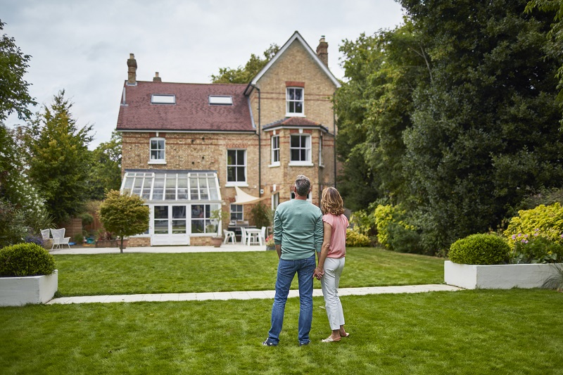 Rear view of mature couple looking at house. Man and woman are holding hands while standing on grassy field. They are wearing casuals.