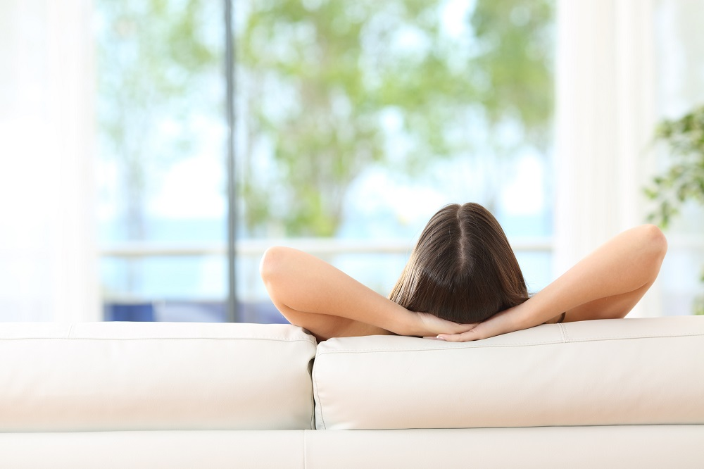 Rear view of a woman relaxing sitting on a couch with the hands on the head and looking outdoors through the window of the livingroom at home